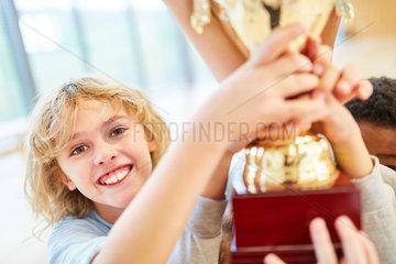 Junge als Sieger bekommt einen Pokal
