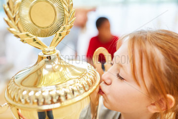 Maedchen gibt Sieger Pokal einen Kuss