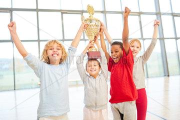 Erfolgreiches Kinder Team mit Pokal jubelt