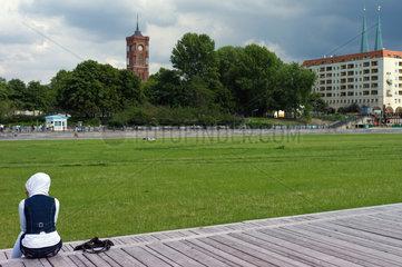 Berlin  Deutschland  eine Frau mit Kopftuch sitzt auf dem Schlossplatz