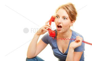 Frau am Telefon schaut erschrocken beim Telefonieren