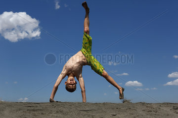 Bolsena  Italien  ein Junge schlaegt am Strand vor Freude ein Rad