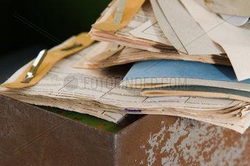 alte Bueropapiere auf verrosteter Kassette