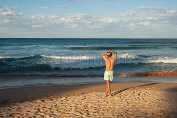 Sydney  Australien  Junger Mann am Strand von Manly