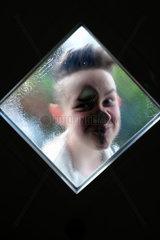 Berlin  Deutschland  Junge schaut durch das Fenster einer Haustuer