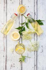 Homemade elderflower sirup  lemon slices  leaves and elderflower