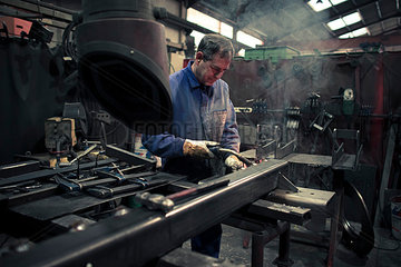 Welder welding metal in a factory
