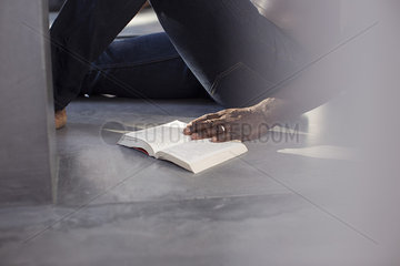 Man reading book on floor  cropped