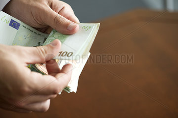 Hands counting stack of cash  cropped