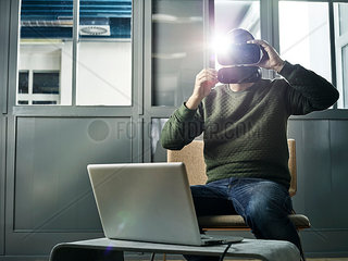 Man working with VR glasses and laptop