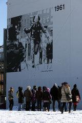 Berlin  Deutschland  Menschen stehen vor einer Informationstafel zum Bau der Berliner Mauer