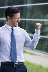 Businessman clenching fist in victory