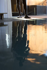 Man's reflection on spa swimming pool  low section
