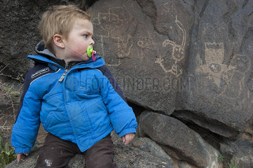 Toddler boy studying petroglyph in Yellowstone National Park  USA