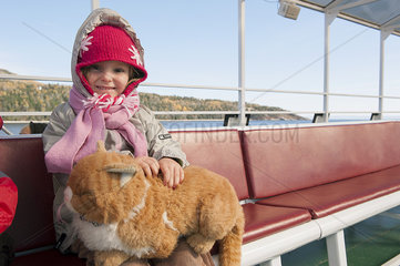 Little girl sitting on ferry boat with stuffed cat on her lap  portrait