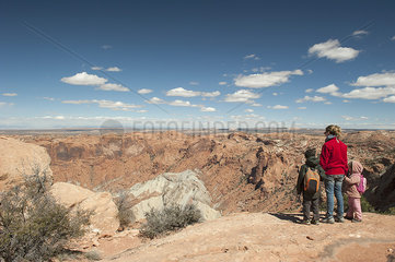 Mother and children standing at edge of canyon in Canyonlands National Park  Utah  USA