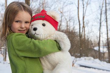 Little girl hugging teddy bear outdoors in winter