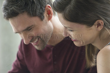 Couple relaxing together  both looking down and smiling