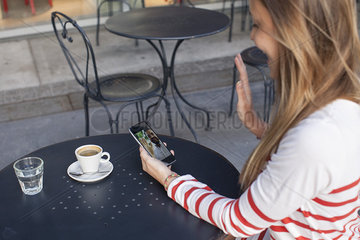 Young woman using smartphone to video chat in cafe