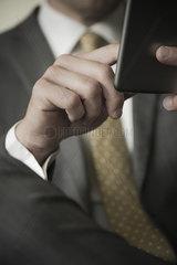 Businessman using wireless device  cropped