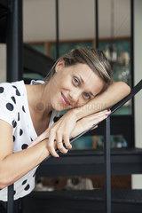 Woman leaning against bannister  portrait