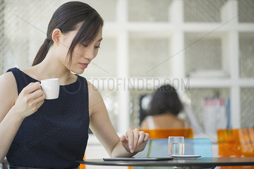 Woman relaxing in cafe with digital tablet