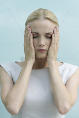 Woman with hands on face  eyes closed