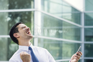 Businessman holding cell phone and celebrating good news