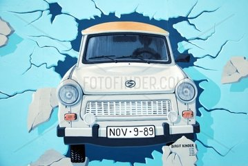 east german trabant car dirving through the berlin wall. graffiti on east side gallery berlin.