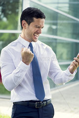 Businessman looking at cell phone and making victorious gesture