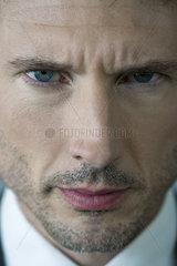 Businessman glaring with furrowed brow  portrait