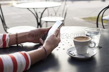 Young woman using smartphone in cafe  cropped