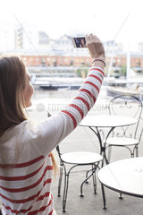 Young woman posing for a selfie at sidewalk cafe