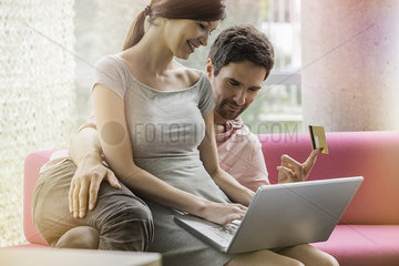 Couple shopping online from home computer