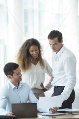 Office worker showing document to colleagues