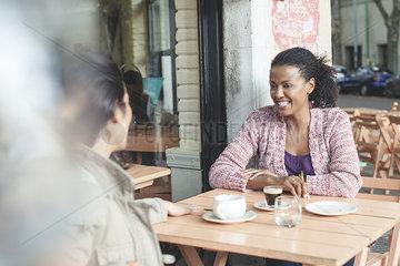 Friends talking at sidewalk cafe