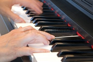 two hands playing the piano