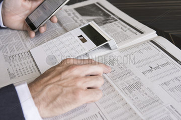 Checking stock market performance using smartphone and newspaper