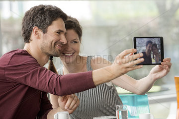 Couple smiling for selfie taken with digital tablet