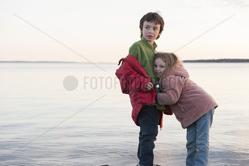 Little girl hugging her brother at water's edge