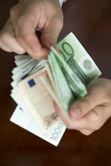 Hands counting stack of cash