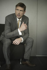 Businessman sitting in waiting room chair with worried expression on face
