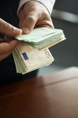Man counting stack of cash  cropped