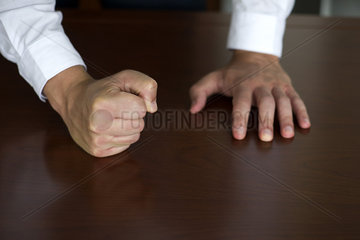 Businessman pounding fist on table  cropped