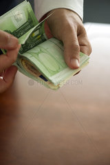 Man counting stack of money  cropped