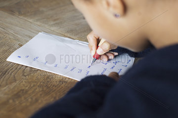 Girl writing in cursive on paper  cropped