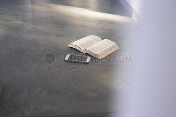 Smartphone and open book lying on floor