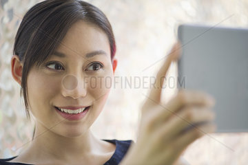 Woman taking a photograph with a digital tablet