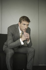 Businessman sitting with hands under chin and worried expression on face