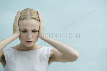 Woman holding hands over ears  looking down with furrowed brow